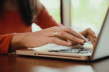 Mujer-tecleando-sobre-laptop trabajo trabajadora